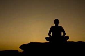 Silhouette of man practicing relaxation techniques