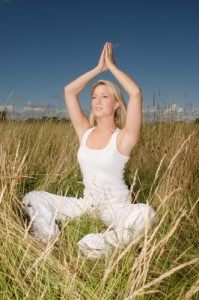 woman doing meditation on grass area
